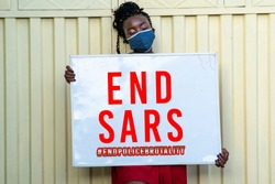 A millennial African woman wearing face mask and holding a sign with end SARS inscription - concept on human rights and police brutality