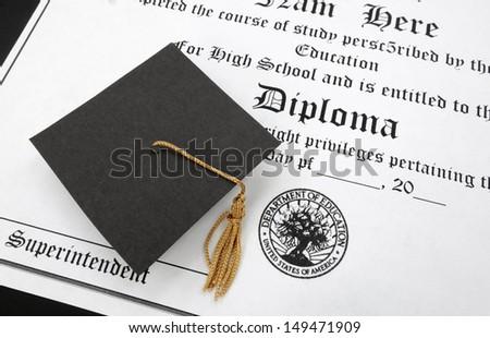 a mini gradaution cap on a high school diploma