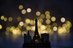 A miniature copy of the Notre Dame de Paris, the Eiffel Tower, and the Arch of Triumph in the bokeh effect lights background, a trip to Paris