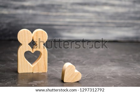 A miniature couple in love and a heart near them. The concept of family problems and loss of feelings for your loved one. Consultation family psychologist. Rupture / divorce. Selective focus #1297312792