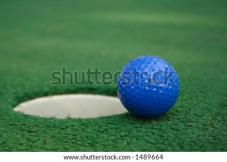 A miniature golf ball near the hole