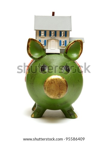 A miniature house rests on a piggy bank for monetary concepts.