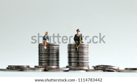 A miniature man and a miniature woman sitting on a stack of coins of the same height.