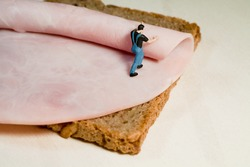 A miniature model workman rolls out a slice of ham on a slice of brown bread, back view with copyspace.