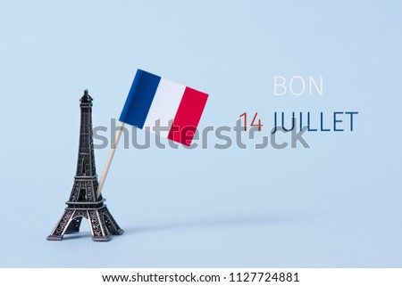 a miniature of the Eiffel Tower, a french flag and the text bon 14 juillet, happy 14 july, the national day of France written in French, against a pale blue background