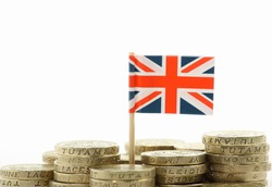 A miniature Union Jack, the flag of Great Britain, stands behind stacks of British Pound Coins on a white background with copy space
