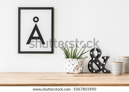 A minimalist, aesthetic letter poster in a frame on a white wall above a led letter light and aloe in fabric planter #1067803490