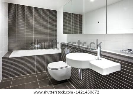A minimalistic bathroom featuring a bathtub, a sink, a wall-mount toilet seat, and mirrors #1421450672