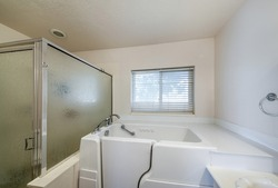 A minimalistic bathroom interior with a standing bathtub for elderly accessibility in white color