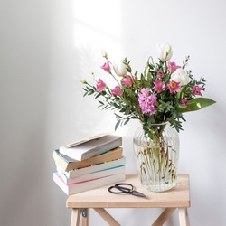 A minimalistic bouquet of white tulips, pink eustoma, hyacinth, eucalyptus in a fluted glass vase on a white panel of an artificial fireplace. Empty space. A stack of books and scissors.
