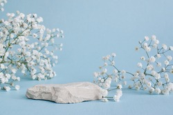 A minimalistic scene of a lying stone with flowers on a light blue background. Catwalk for the presentation of products and cosmetics. Showcase with a stage for natural products.