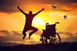 A miracle happened. Disabled handicapped man is healthy again. He is happy and jumping at sunset.