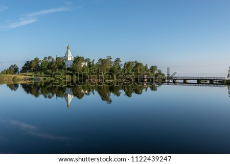 A mirror reflection of the Nikolsky monastery in the calm water of the lake. Valaam is a cozy and quiet piece of land, the rocky shores of which rise above the lush waters of lake Ladoga #1122439247