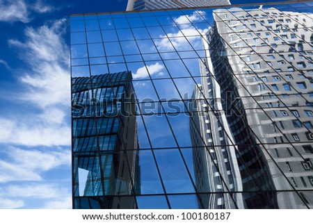 a mirrored building reflected the blue sky