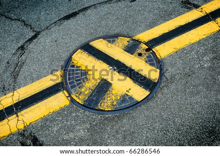 A mis-aligned manhole cover. Symbolizes shoddy work, incompetence.
