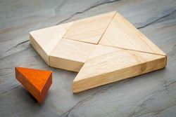 a missing piece in a square built from tangram shapes, a traditional Chinese puzzle game, slate rock background