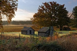 A misty morning at Valley Forge National Historic Park located in Valley Forge, Pennsylvania, USA. The buildings are reproductions of cabins used by Revolutionary War soldiers.
