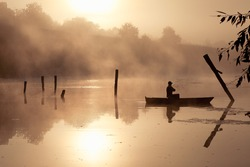 A misty morning by the lake. Small fishing boat at the lake.  Space for text.