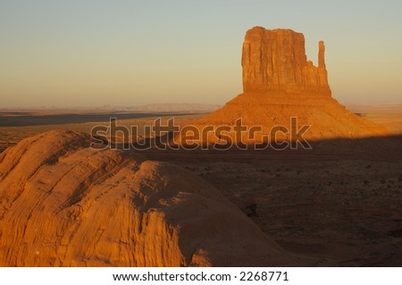 A mitten mesa lit up by the setting sun in Monument Valley park (Navajo Nation) with a boulder in the foreground.