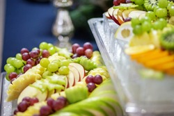 A mix of fruits from grapes, apples, grapes, oranges. The concept is healthy food, party, buffet, catering.