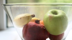 a mix of whole fruits refreshed with water lies in a large glass dish with the texture of water drops on a transparent surface on the kitchen table against the background of a summer window