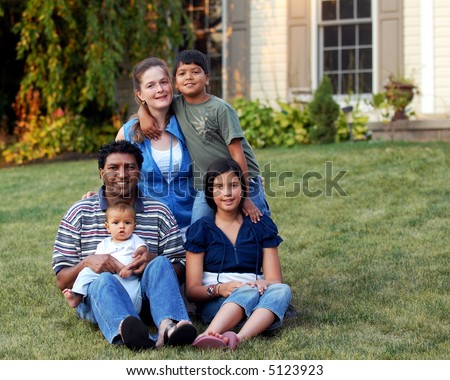 A mixed-race family of five on the lawn of their suburban home.