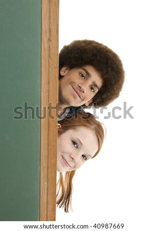 A mixed-race teenage boy and a teenage girl behind a blank chalkboard with room for copy