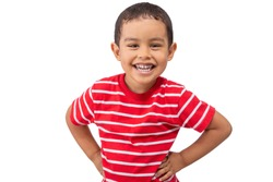 A mixed race young boy laughs while looking at the camera. The toddler wears a red white striped shirt as he smiles at the camera with hands on his hips.