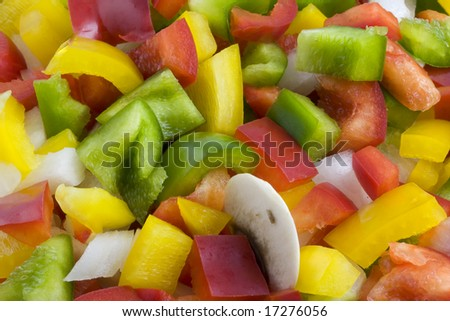 a mixture of green, red, yellow bell pepper, onion and mushrooms diced and ready for cooking or salad