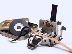 A 16mm film cutter has a film placed on top and a roll of film and a can for packing on the side, Film spilcer