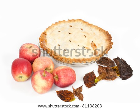 A 100mm macro angled  studio shot of a homemade apple pie with apples and autumn leaves on a white background.
