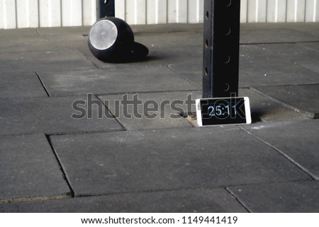 a mobile phone with a timer and a metal dumbbell for classes on the backdrop of a gym where you practice fitness, sports and recreation   #1149441419