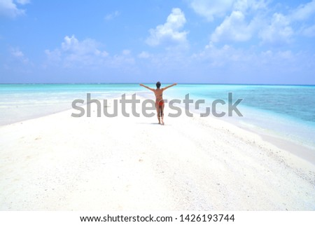 A model enjoys life on a sand bank in Maldive. Paradise on Earth with deserted beaches. Suntanning and relaxing under the tropical sun.  #1426193744
