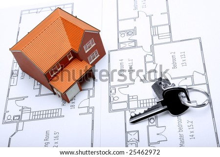 A model home and house key on architectural floor plans for an extension.