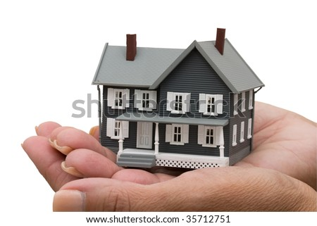 A model house sitting in hands isolated on a white background with clipping path, mortgage help