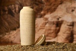 A model of a Jar used for the Dead Sea scrolls against a blurred background of the Qumran caves