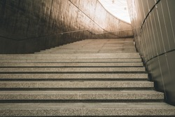 a modern architecture loft concept design of concrete stair with granite surface texture at the walking entrance of a modern exhibition hall building with a sun light at the end of the tunnel.