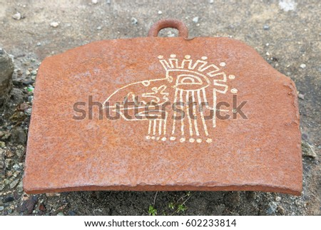 A modern Aztec figurine inscribed on a metal platform in an abandoned shipyard/Modern Aztec Graffiti/An Aztec figurine inscribed on a metal platform in a shipyard.  #602233814