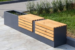 A modern bench with a flower bed in a city park on a sunny day. City improvement, urban planning, public spaces.