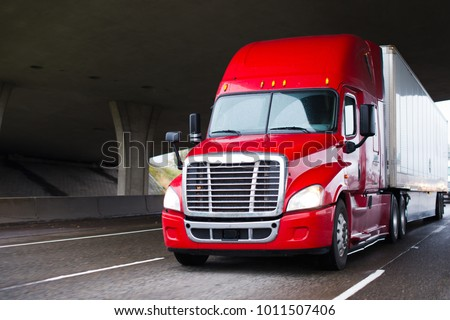 A modern big rig semi truck for long haulage with a high cabin for improving aerodynamic characteristics moves under the bridge transporting a dry van semi trailer with commercial cargo