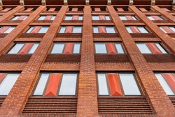 A modern building facade made with orange bricks. A pattern of windows features the edifice facade. This hotel exterior is an exmple of contemporary, Swedish industrial construction - Malmo, Sweden
