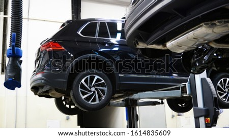 A modern car SUV in a service center is lifted on a lift for diagnosics, maintenance or repair. New shiny expensive off-road car in service. Concept.