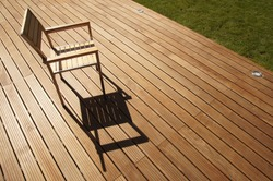 a modern chair on an exotic wood terrace on a sunny afternoon
