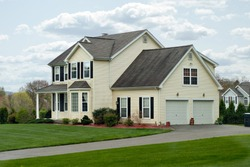 A modern colonial style residential suburban home with a small porch and a two car garage.