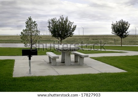 A modern concrete picnic spot at a Wyoming interstate rest area with a power plant in the background.