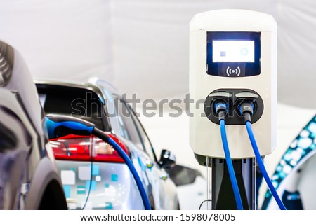 A modern electrical fast charger for the electrical or hybrid PHEV automobiles. An Energy power of future. Ecology friendly charger concept. Home electric car battery charger.