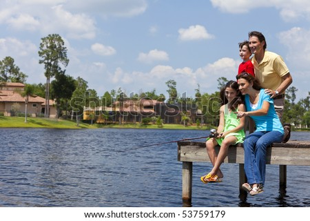 A modern family of mother, father, children, son and daughter fishing in a lake off a jetty on a sunny day