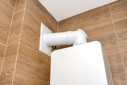 A modern gas boiler for natural gas, installed in a boiler room lined with ceramic tiles, visible pipe leading flue gas to the chimney.