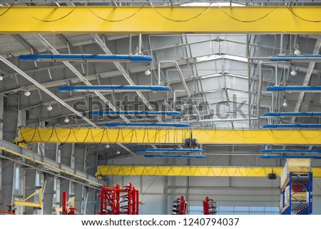 A modern industrial workshop, three overhead cranes under the ceiling. #1240794037
