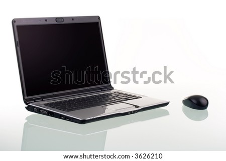 A modern laptop computer and wireless mouse with reflection on a glass surface.
